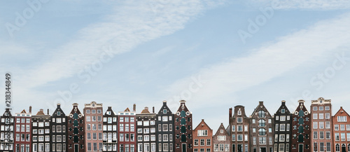 Poster Amsterdam Panorama or panoramic view. Traditional houses in Amsterdam in the Netherlands in a row against the blue sky.