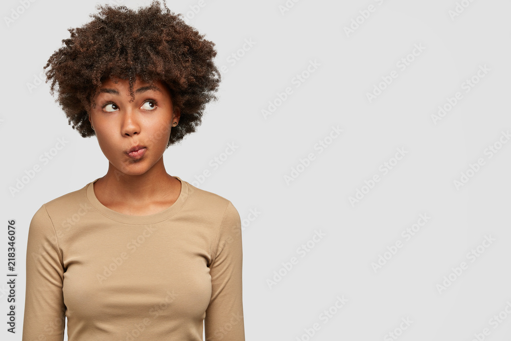 Fototapety, obrazy: Young lovely female has dark skin, clueless and unaware expression, purses lips as being questionned, looks with puzzlement upwards, isolated over white background with copy space on right side