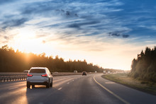 Highway Traffic In Sunset. Road With Metal Safety Barrier Or Rail. Cars On The Asphalt Under The Cloudy Sky