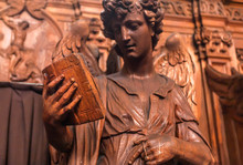 Reading Angel Holding An Old Book, Wooden Statue In 17th Century Catholic Church Saint Charles Borromeo In Antwerp