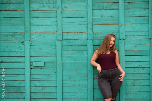 Fotografie, Tablou blond girl model plus size on the background of a green wall