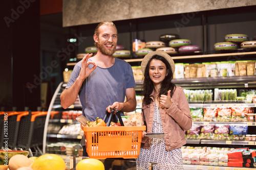 Plakat Młody uśmiechnięty facet i śliczna dziewczyna w kapeluszu z listą zakupów w ręce szczęśliwie patrzeje w kamerze z koszykowy pełnym produkty w supermarkecie