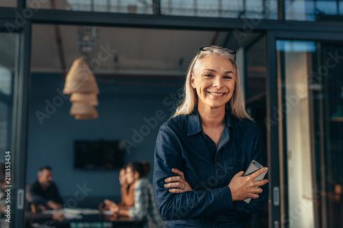 Fototapeta Smiling senior woman standing in office doorway obraz