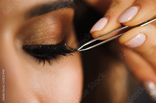 Canvas Print Close up of professional stylist lengthening lashes for female client in a beauty salon