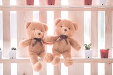 Two Brown Teddy Dolls Sitting Together On Wood Shelf