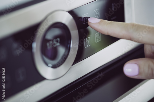 Female finger is touching the button of modern panel of electric oven.