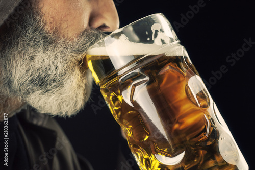 Fotomural A bearded friar (Franciscan religious man) eagerly drinking cold beer from a giant mug