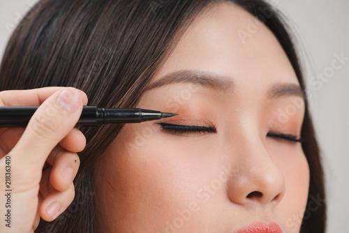makeup beauty with brush eye liner on pretty woman face Fototapeta