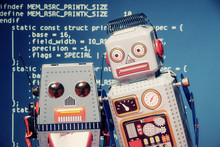 Two Tin Toy Robots Standing Still Like In A Selfie Shot. Background: Computer Source Code (public Domain), White On Blue.
