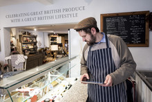 Bearded Man Wearing Flat Cap And Apron Standing At Counter In A Delicatessen, Holding Digital Tablet.
