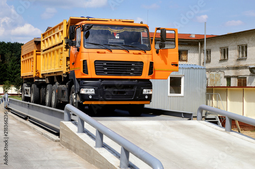Fotografija  orange truck with grain is weighed on the scales in the grain storage area