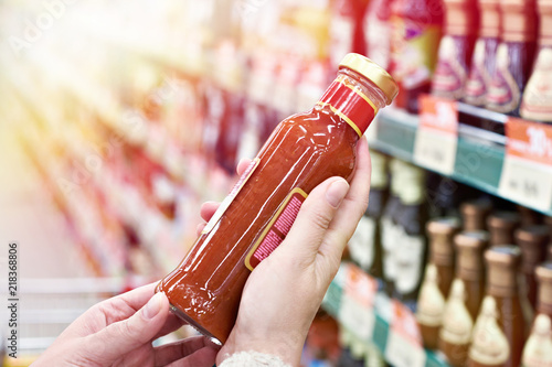 Foto op Plexiglas Kruiderij Buyer hands with bottle of chilli sauce in store
