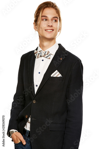76cc5bfe78 A young man in a black suit jacket and button up shirt, accessorized with a  striped bow tie and pocket square. The blond smiling while looking aside  over ...