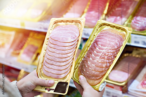 Woman chooses slice of ham at store