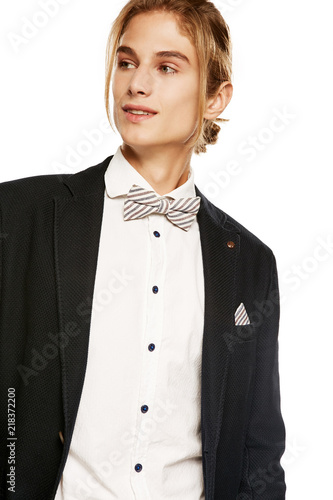 4de0482bcc A handsome young man wearing a black suit jacket and button up shirt,  accessorized with a striped bow tie and pocket square. The blond guy with a  ponytail ...