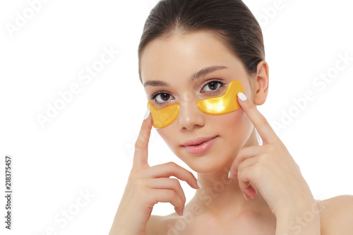 Photo Woman face with golden mask under eyes, natural makeup