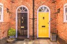 Two Residential Front Doors, One Yellow, One Black With A Drain Pipe Down The Middle. The Walls Are Red Brick There Are Two Side Windows And Lunette Arches Over The Doors