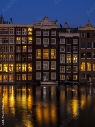 Photo  Historic buildings on the Damrak canal in the centre of beautiful Amsterdam at night