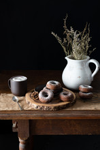 Chocolate Donuts On A Rustic Farmhouse Table