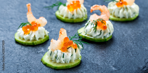 Fotografia Appetizer canape with red caviar, shrimp and cream cheese on stone slate background close up