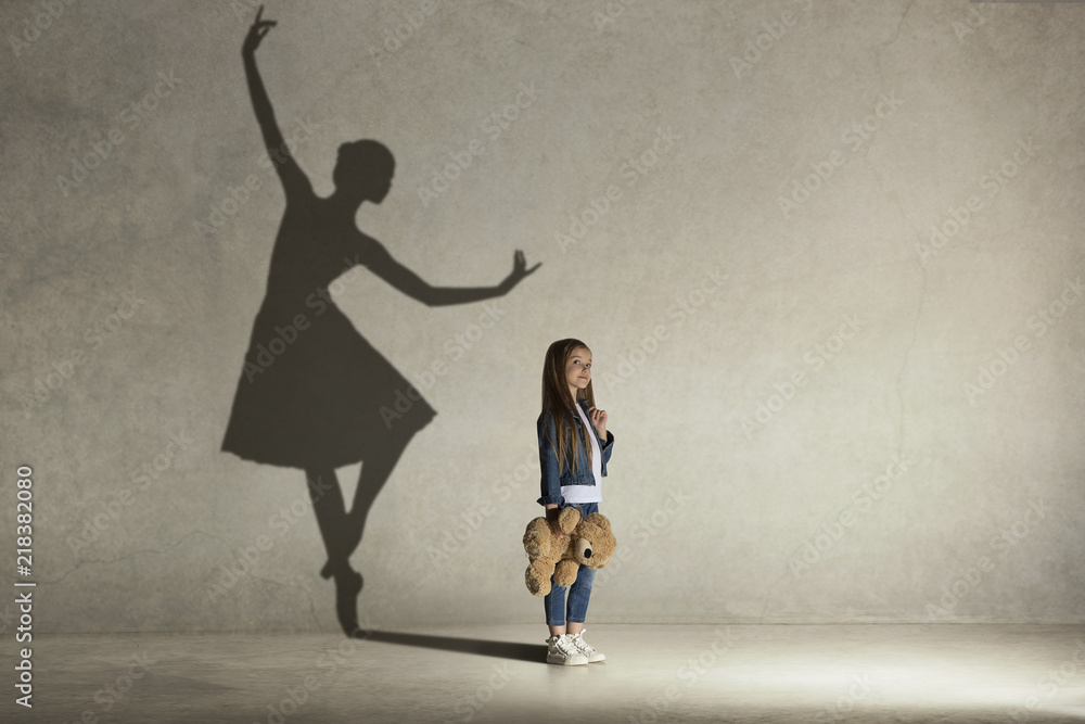 Fototapeta Baby girl dreaming about dancing ballet. Childhood and dream concept. Conceptual image with shadow of ballerina on the studio wall
