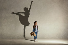 Baby Girl Dreaming About Dancing Ballet. Childhood And Dream Concept. Conceptual Image With Shadow Of Ballerina On The Studio Wall