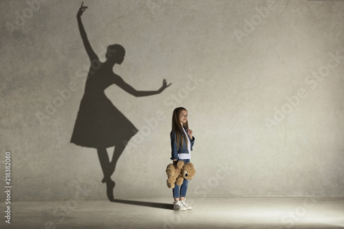 Fototapeta Baby girl dreaming about dancing ballet. Childhood and dream concept. Conceptual image with shadow of ballerina on the studio wall obraz