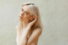 Blonde Girl Posing On White Wall