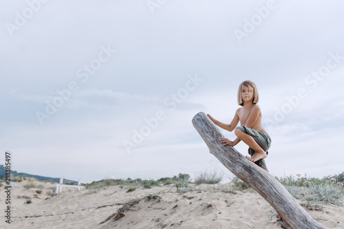 Boy with long hair on the log like Mowgli Canvas Print