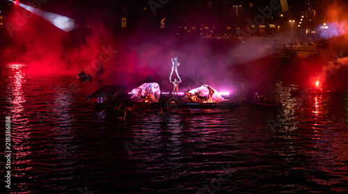 Acrobat suspended just above the performance with red and purple ligts