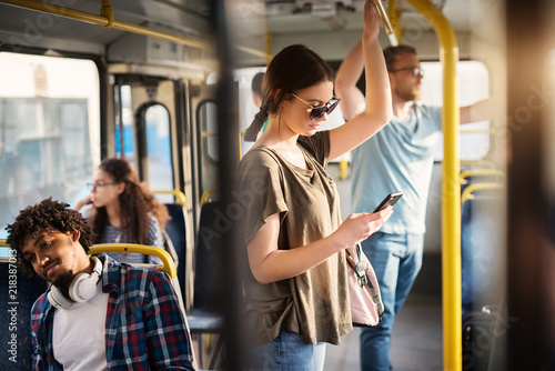 Sweet girl with sunglasses in using phone while standing in a bus.