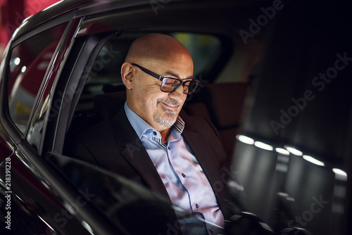 Mature satisfied businessman is looking at his laptop while driving on a back seat in a car Wallpaper Mural