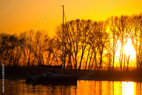 Photo  Yacht sailing against sunset. yellow sunset light