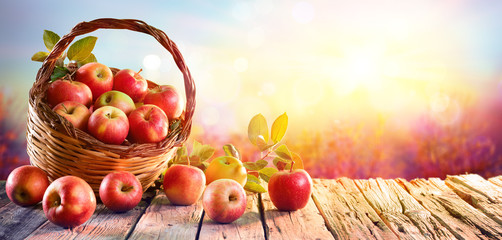 Red Apples In Basket On Aged Table At Sunset