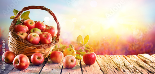 Tuinposter Vruchten Red Apples In Basket On Aged Table At Sunset
