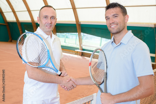 Obraz Two men shaking hands on tennis court - fototapety do salonu