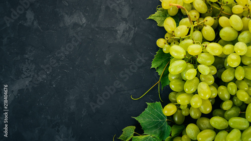Foto  Green grapes with leaves of grapes on a stone table