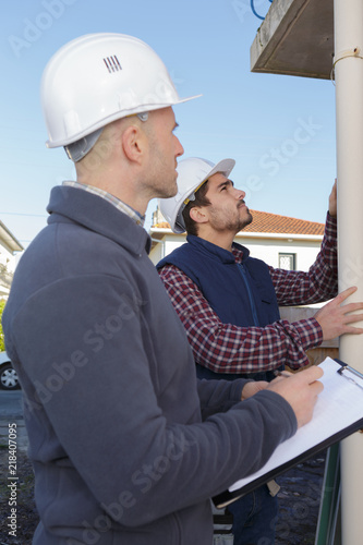 Fotografia, Obraz  Workmen assessing drainpipe on outside of building