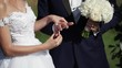 Wedding couple put on wedding rings at ceremony outdoors at summer sunny day