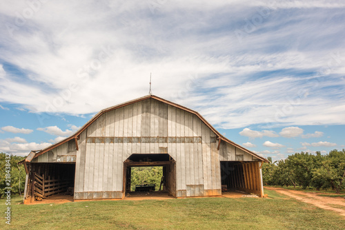 Fotografia, Obraz An old, beautiful barn that holds farm equipment stands regally on the side of the road in rural, upstate South Carolina