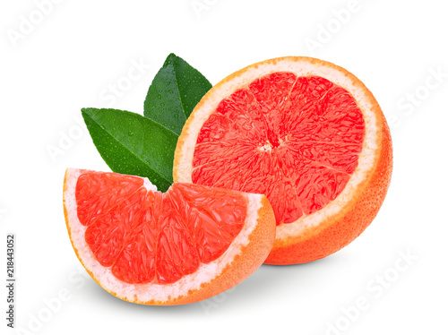 half and sliced grapefruit with green leaves isolated on white background