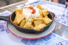 Famous Spanish Dish, Patatas Bravas, Or Spice Potatoes, Served Beautifully On A Table With White Wine In Barcelona.