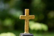 The Metal Cross Is A Symbol Of Orthodoxy. Orthodox Cross On A Beautiful Green Blured Bokeh Background. The Orthodox Symbol Is The Byzantine Sign Of Orthodoxy With An Oblique Cross.