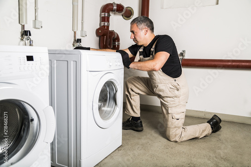 Printed kitchen splashbacks Artist KB Plumber in uniform repairs inside washing machine in laundry