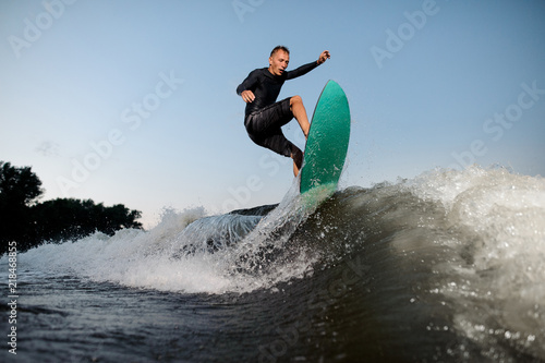 Obraz Active and young wake surfer jumping on a wake board down the river - fototapety do salonu