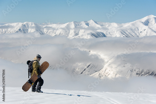 man in warm ski equipment slowly wanders against the background of snowy mountains