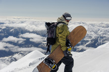 Man In Ski Equipment, Wearing Safety Glasses, Rises To A Snowy Mountain Against A Cloudy Sky