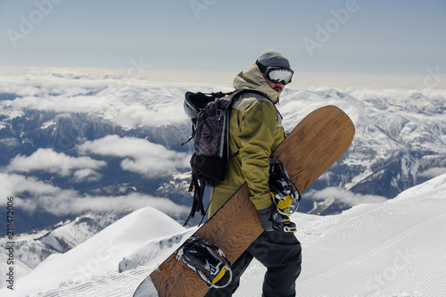 obraz dibond man in ski equipment, wearing safety glasses, rises to a snowy mountain against a cloudy sky