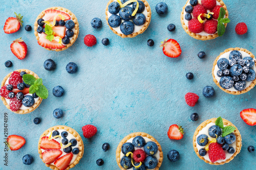 Tasty berry tartlets or cake with cream cheese and different berries around. Pastry dessert top view.