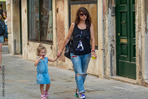 Photo Young aunt and her little niece walking in Venice